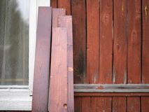 Planks leaned against a wooden wall. New painted planks leaned against a wooden wall of old house stock photos