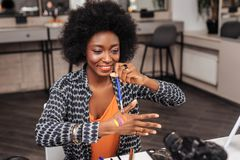 Beautiful dark-skinned african american woman with a gold bracelet demonstrating new swatches to the audience stock image