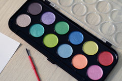 New palette of watercolors with pearl shade, brush and paper Stock Photography