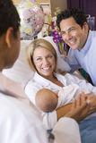 New parents with baby talking to doctor Stock Image