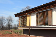 New passive house with blinds. New modern one story house with large windows. Eco living. Wooden enetian blinds Stock Images