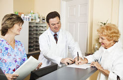 New Patient Sign In. Doctor and nurse greating a new patient as she signs in.  Focus on doctor Royalty Free Stock Photo