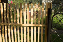 New picket fence and black metal gate for protection and safety in the garden Stock Photos