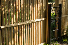 New picket fence and black metal gate for protection and safety in the garden Stock Image