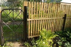 New picket fence and black metal gate for protection and safety in the garden Royalty Free Stock Photography