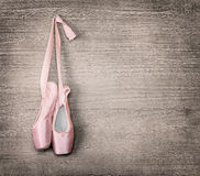 New pink ballet shoes. Hanging on wooden background.Vintage style stock images