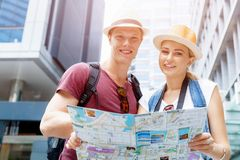 New places to explore. Happy young couple as tourists with a map Royalty Free Stock Photography