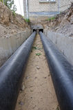 New plastic modern heating pipes in trench near city house Stock Photos