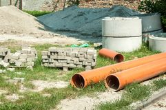 New plastic water pipes for city pipeline system paving tiles concrete blocks for sewerage and pile of sand and gravel on the stre. Et reconstruction site stock photography