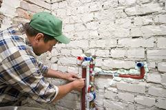 New plumbing. A plumber installing new plumbing in a renovated and reconstructed bathroom Stock Images