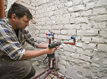 New plumbing. A plumber installing new plumbing in a renovated and reconstructed bathroom Royalty Free Stock Photos