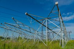 New poles for power lines lying on the ground. For the next installation in the design position. Royalty Free Stock Image
