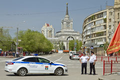 New police car and the police are standing in the cordon at the victory parade near the Central train station Volgograd-1 Stock Photos