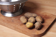 New potatoes. Jersey Royal new potatoes on a wooden chopping board with a metal colander in the background Royalty Free Stock Images