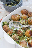 New potatoes with avocado salsa. In oven dish with mortar and pestle Royalty Free Stock Photo