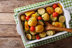 New potatoes baked with zucchini, bell pepper and tomatoes close Stock Photo