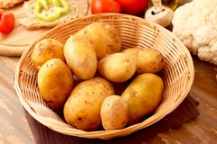 New potatoes in a basket. Potatoes placed in a basket with different vegetables in the background Stock Photo