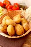 New potatoes in a basket. Potatoes placed in a basket with different vegetables in the background Royalty Free Stock Images