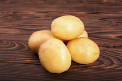New potatoes on a dark brown wooden background. Delicious, family-favorite vegetable is good for you. A heap of young potatoes. royalty free stock photo