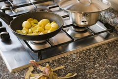 New potatoes frying in pan with the peels in foreground Stock Photography