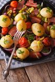 New potatoes with onions and bacon on a plate. Vertical, rustic Royalty Free Stock Images