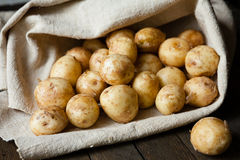 New potatoes with the peel on the table in a bag Stock Photos