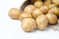 New potatoes in a sack on a white background, selective focus Stock Photos