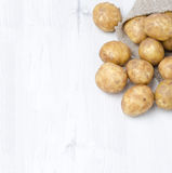 New potatoes in a sack on a white wooden  background (with space Royalty Free Stock Photography