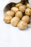 New potatoes in sack on a white wooden board and space for text Royalty Free Stock Photography