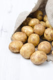 New potatoes in a sack on a white wooden board Stock Image
