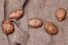 New potatoes on sackcloth on wooden table, top view. Closeup Royalty Free Stock Photos