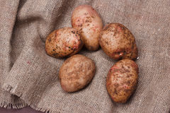 New potatoes on sackcloth on wooden table, top view. Closeup Stock Photography