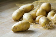 New potatoes on a wooden kitchen board Stock Photo