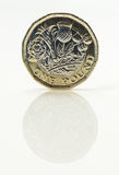 New Pound Coin - front side. New United Kingdom pound coin balanced on reflective high gloss white surface stock image