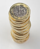 New Pound Coin - tall stack from above. New United Kingdom pound coin tall stack on a high gloss white surface stock images