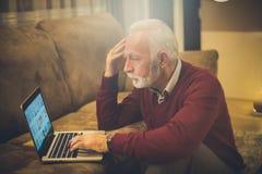 New problem arose. Senior man at home using laptop stock image