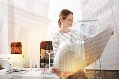 Positive female eco engineer studying a blueprint Stock Image