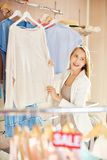 New pullover. Beautiful young woman choosing new pullover Royalty Free Stock Photo