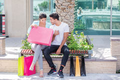 New purchase. Couple sitting on a bench and holding shopping bag Royalty Free Stock Photo