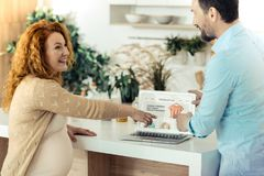 Amused pregnant woman pointing at the monitor. New purchase. Delighted pregnant women looking at her husband while pointing at the clothes on the internet shop royalty free stock images