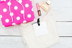New purchases and pink shopping bag. Flat lay Stock Image
