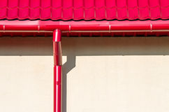 New rain water downspout on wall. Red tiled roof with new rain water downspout against wall stock images