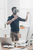 New reality is here!. Handsome young man in VR headset gesturing while standing in creative office Stock Image