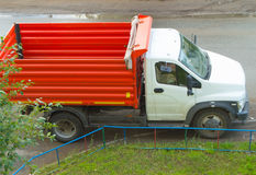 New red dump truck with white cab is empty, ready for transportation.  Stock Photo