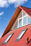New red metal roof with attic windows skylights and Ventilation pipe for heat control. Stock Photos