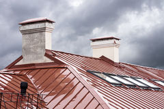 New red metal roof with skylights in rain Stock Image