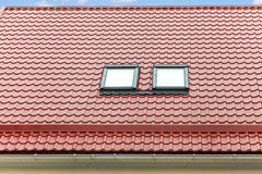 New red metal roof with skylights and rain gutter. Royalty Free Stock Photos