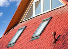 New red metal roof with windows skylights and ventilator for heat controlю Royalty Free Stock Image