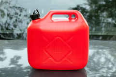 New red plastic jerrycan stands on car hood Royalty Free Stock Image
