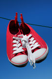 New red sneakers on washing line Royalty Free Stock Image